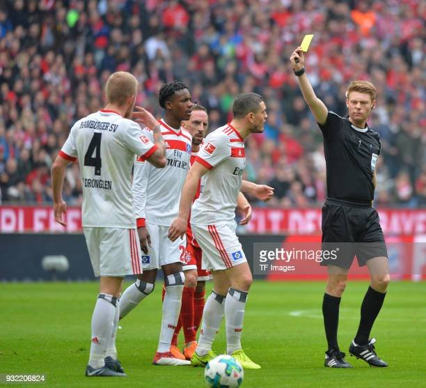 Referee Christian Dingert shows a yellow card to Rick van Drongelen of Hamburg during the Bundesliga match between FC Bayern Muenchen and Hamburger...