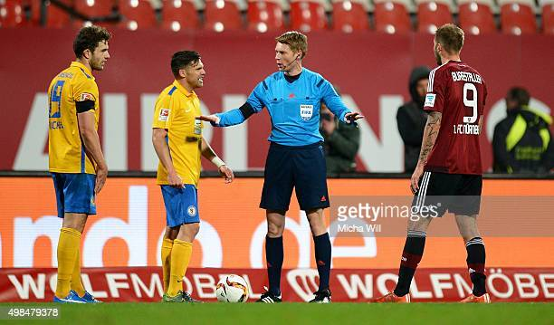 Referee Christian Dingert speaks with Ken Reichel of Braunschweig and Guido Burgstaller of Nuernberg during the Second Bundesliga match between 1 FC...