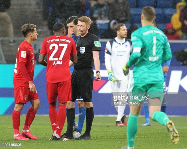 Referee Christian Dingert talks to Bayern Munich's Austrian defender David Alaba after he suspended the German first division Bundesliga football...