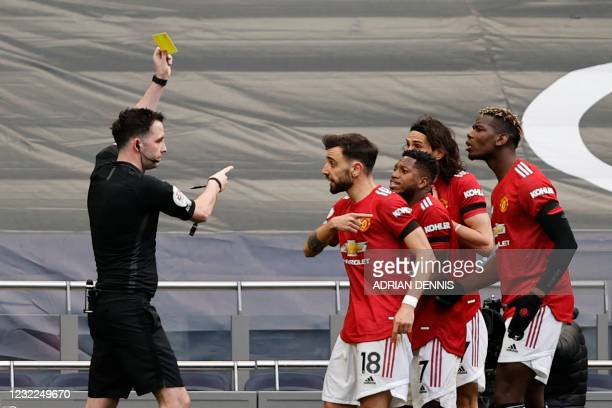Referee Christopher Kavanagh shows a yellow card to Manchester United's Uruguayan striker Edinson Cavani during the English Premier League football...
