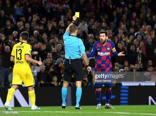 Referee Clement Turpin shows a yellow card to Lionel Messi of FC Barcelona during the UEFA Champions League group F match between FC Barcelona and...