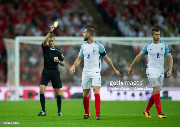 Referee Clement Turpin shows the yellow card to England's Eric Dier during the FIFA 2018 World Cup Qualifier between England and Slovakia at Wembley...