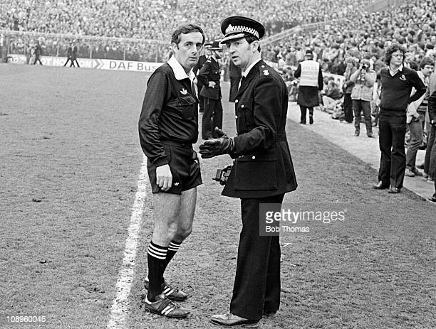 Referee Clive Thomas in discussion with a senior police officer after a pitch invasion during the FA Cup SemiFinal between Wolverhampton Wanderers...