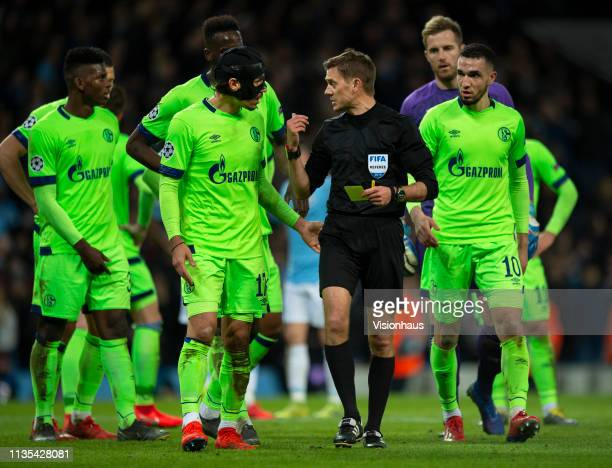 Referee Clément Turpin is confronted by FC Schalke players after awarding a penalty to Manchester City during the UEFA Champions League Round of 16...