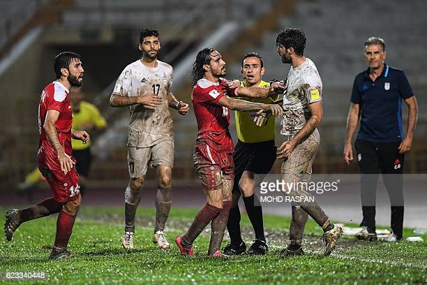 A referee controls Karim Ansari Fard of Iran and Alaa Al Shbbli of Syria after an arguement on the pitch during the 2018 World Cup qualifying...