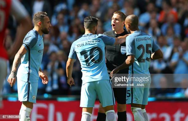 Referee Crag Pawson is surrounded by Nicolas Otamendi Sergio Aguero and Fernandinho of Manchester City during the Emirates FA Cup semifinal match...