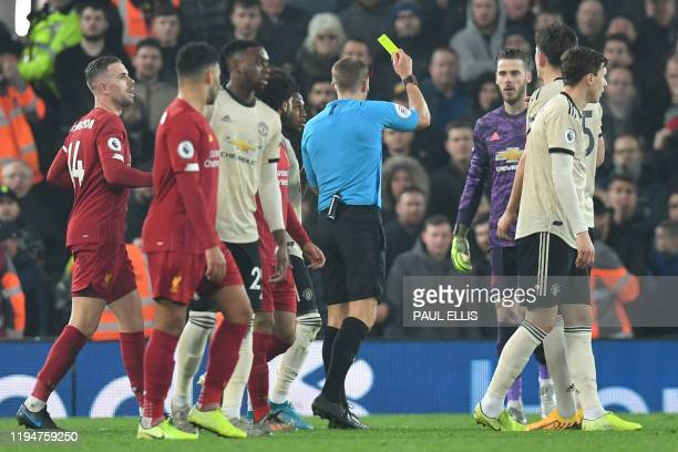 Referee Craig Pawson books Manchester United's Spanish goalkeeper David de Gea for dissent during the English Premier League football match between...
