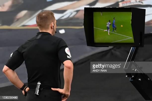 Referee Craig Pawson checks a VAR monitor for a penalty which is given during the English Premier League football match between Tottenham Hotspur and...