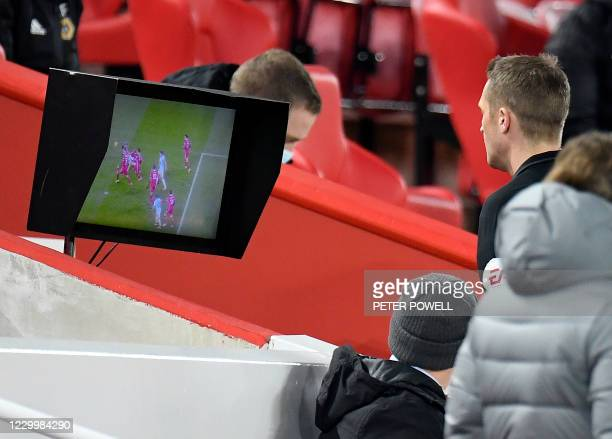Referee Craig Pawson checks the VAR screen during the English Premier League football match between Liverpool and Wolverhampton Wanderers at Anfield...