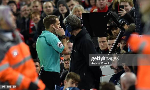 Referee Craig Pawson consults the VAR system during The Emirates FA Cup Fourth Round match between Liverpool and West Bromwich Albion at Anfield on...