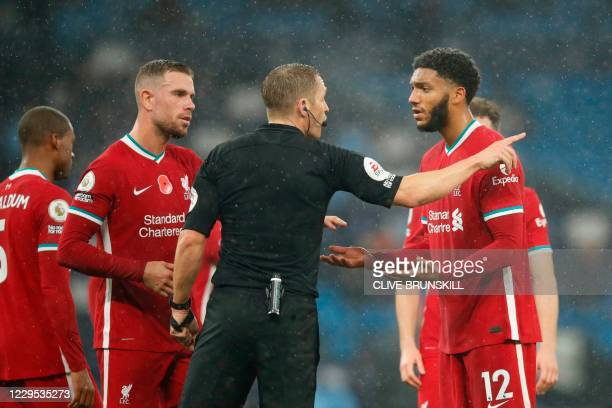 Referee Craig Pawson explains his decision to Liverpool's English defender Joe Gomez who conceded a penalty during the English Premier League...