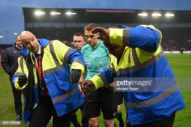 Referee Craig Pawson is escorted off at half time by stewards during the Premier League match between Stoke City and Leicester City at Bet365 Stadium...