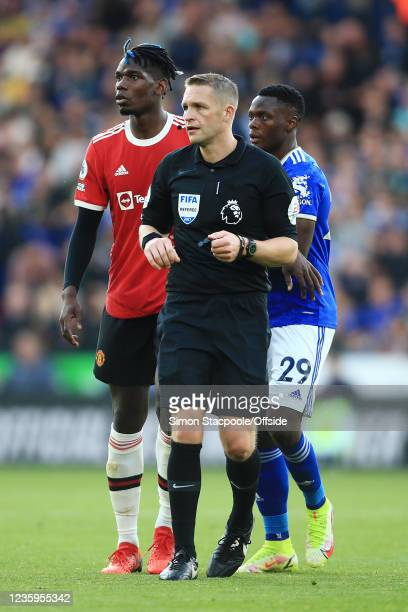 Referee Craig Pawson is followed closely by Paul Pogba of Manchester United and Patson Daka of Leicester City during the Premier League match between...