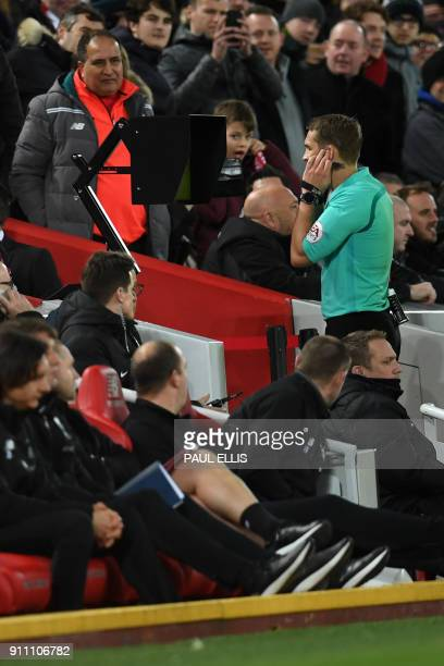Referee Craig Pawson looks at the pitchside screen after speaking to the VAR before giving Liverpool a penalty during the English FA Cup fourth round...