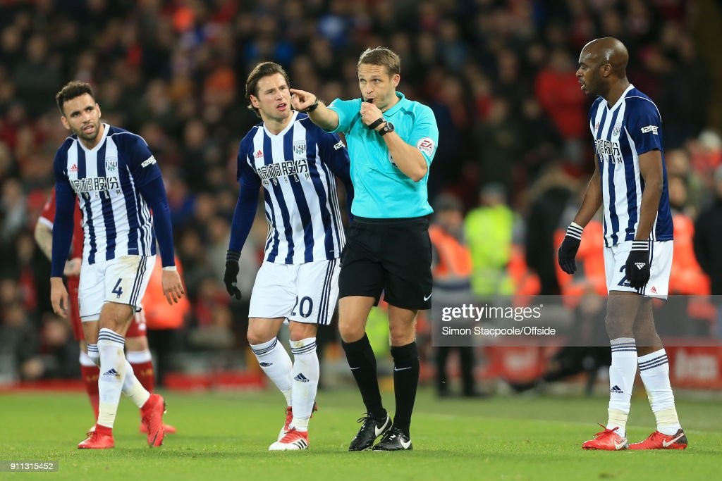 Referee Craig Pawson points to award a penalty following a decision to refer to the Video Assistant Referee (VAR) system as Hal Robson-Kanu of West Brom (L), Grzegorz Krychowiak of West Brom (C) and Allan-Romeo Nyom of West Brom (R) look on during The Emirates FA Cup Fourth Round match between Liverpool and West Bromwich Albion at Anfield on January 27, 2018 in Liverpool, England.