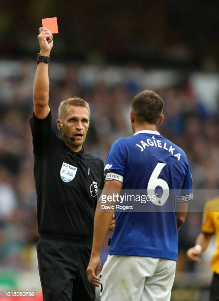 Referee Craig Pawson shows Phil Jagielka of Everton a Red Card during the Premier League match between Wolverhampton Wanderers and Everton FC at...