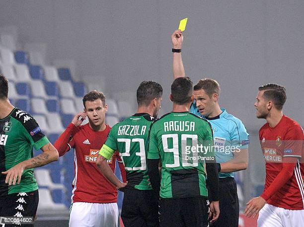 Referee Craig Pawson shows the yellow card to Marcello Gazzola of US Sassuolo Calcio during the UEFA Europa League match between US Sassuolo Calcio...