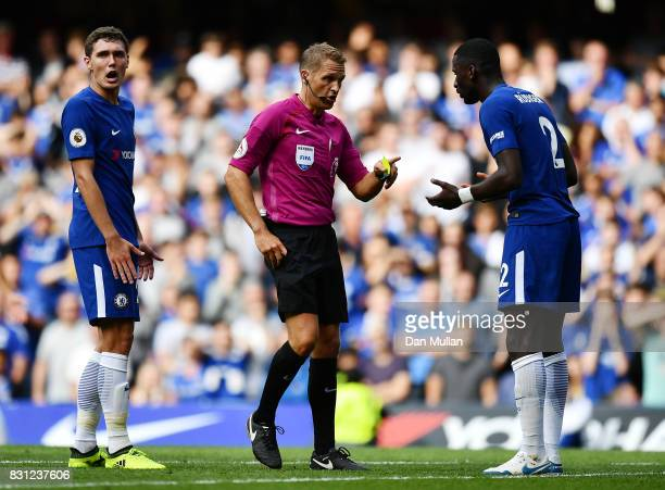 Referee Craig Pawson talks with Antonio Rudiger of Chelsea after showing him a yellow card during the Premier League match between Chelsea and...