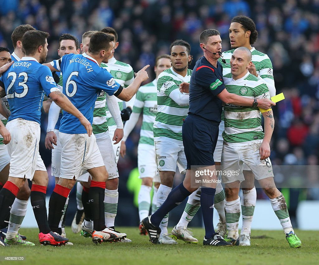 Referee Craig Thomson holds back Celtic's captain Scott Brown during the Scottish League Cup Semi-Final football match between Celtic and Rangers at Hampden Park on February 01, 2015 in Glasgow, Scotland.