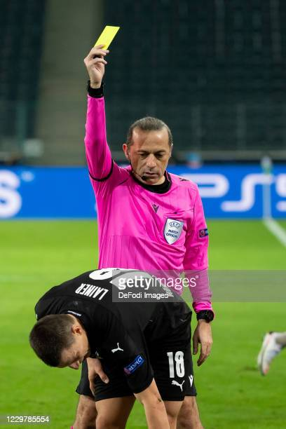 referee Cueneyt Cakir shows Stefan Lainer of Borussia Moenchengladbach the yellow card during the UEFA Champions League Group B stage match between...
