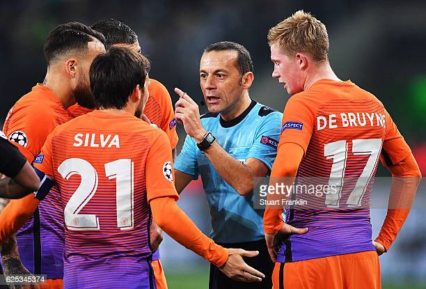 Referee Cueneyt Cakir speaks to David Silva of Manchester City during the UEFA Champions League match between VfL Borussia Moenchengladbach and...