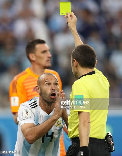 Referee Cuneyt Cakir gives a yellow racd to Javier Mascherano of argduring the 2018 FIFA World Cup Russia group D match between Nigeria and Argentina...