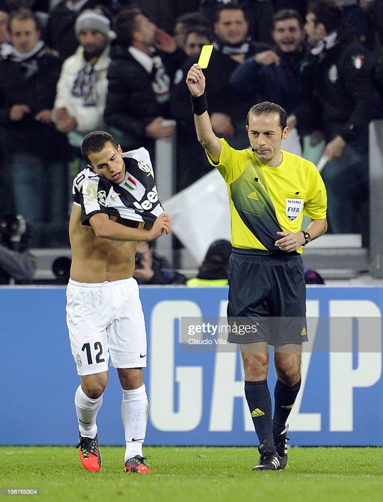 Referee Cuneyt Cakir issues Sebastian Giovinco of Juventus FC with a yellow card for removing his shirt whilst celebrating during the UEFA Champions League Group E match between Juventus and Chelsea FC at Juventus Arena on November 20, 2012 in Turin, Italy.