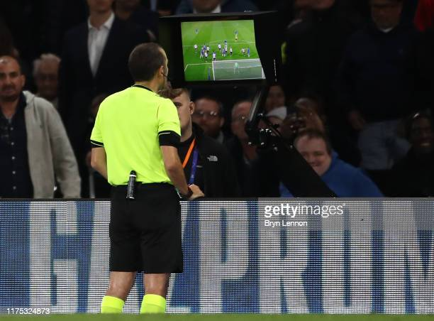 Referee Cuneyt Cakir makes a VAR check during the UEFA Champions League group H match between Chelsea FC and Valencia CF at Stamford Bridge on...