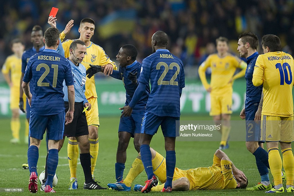 Referee Cuneyt Cakir of Turkey shows red card to Laurent Koscielny (L) of France during the FIFA 2014 World Cup Qualifier Play-off First Leg soccer match between Ukraine and France at the Olympic Stadium on November 15, 2013 in Kiev, Ukraine.