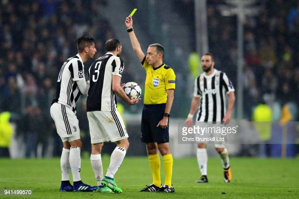 Referee Cuneyt Cakir shows Rodrigo Bentancur of Juventus a yellow card after a foul on Casemiro of Real Madrid during the UEFA Champions League...