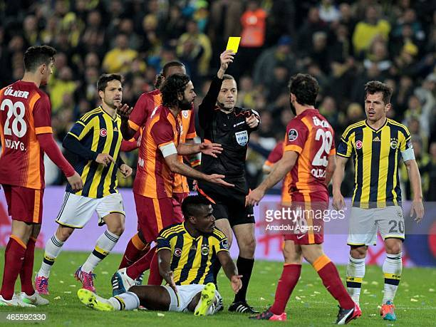 Referee Cuneyt Cakir shows yellow card to Galatasaray's Olcan Adin during Turkish Spor Toto League match between Fenerbahce and Galatasaray at Sukru...