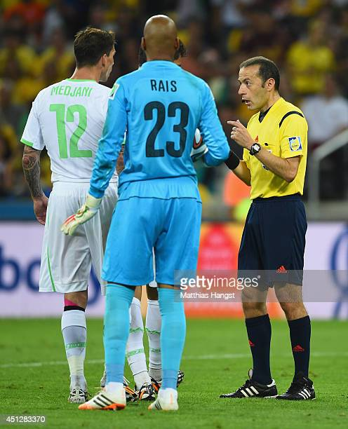 Referee Cuneyt Cakir speaks to Carl Medjani and Rais M'Bolhi of Algeria during the 2014 FIFA World Cup Brazil Group H match between Algeria and...