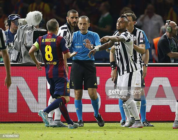 Referee Cuneyt Cakr of Turkey calms down Andres Iniesta of Barcelona and Arturo Vidal of Juventus Turin during the UEFA Champions League Final...