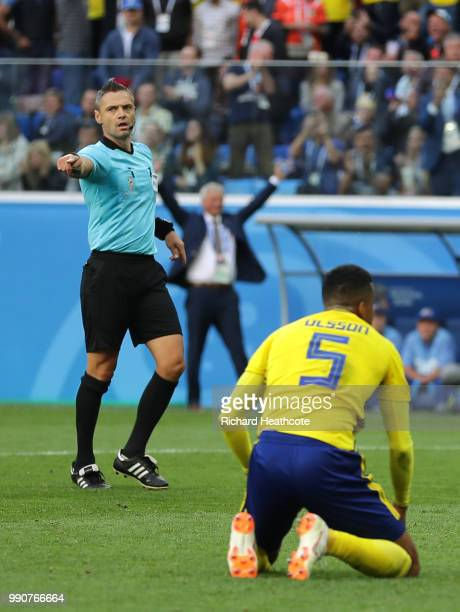 Referee Damir Skomina points the penalty spot for a penalty which will be canceled due to a VAR review during the 2018 FIFA World Cup Russia Round of...