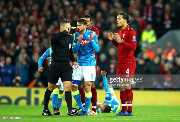 Referee Damir Skomina shows a yellow card to Virgil van Dijk of Liverpool as Fabian of Napoli appeals during the UEFA Champions League Group C match...