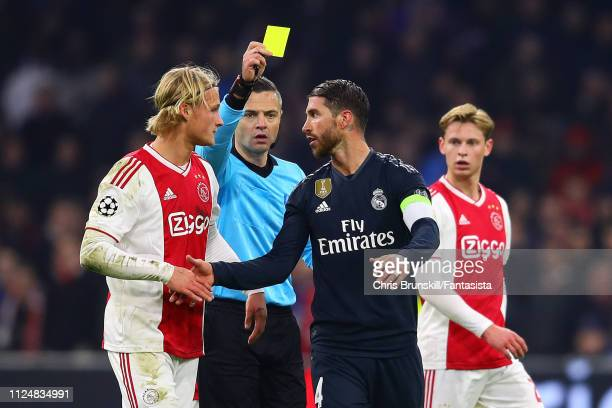 Referee Damir Skomina shows Sergio Ramos of Real Madrid a yellow card during the UEFA Champions League Round of 16 First Leg match between Ajax and...
