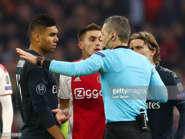 Referee Damir Skomina speaks to Casemiro of Real Madrid and Dusan Tadic of Ajax about a goal that was disallowed for Ajax during the UEFA Champions...