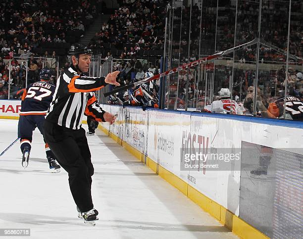 Referee Dan Marouelli takes a stick out of a crack in the glass during the game between the New Jersey Devils and the New York Islanders at the...