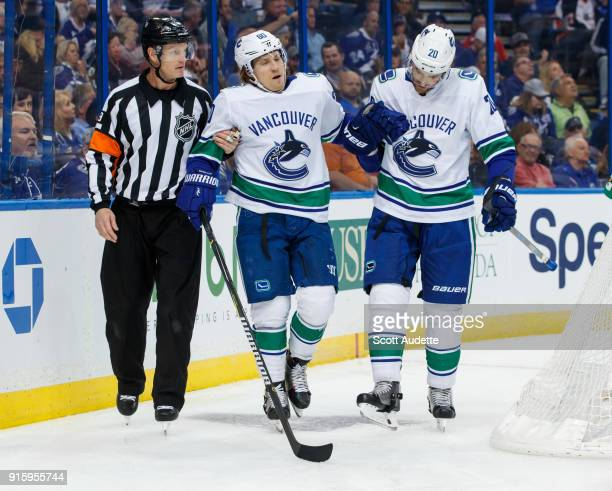 Referee Dan O'Rourke and Brandon Sutter of the Vancouver Canucks help Markus Granlund off after a minor injury during the second period at Amalie...