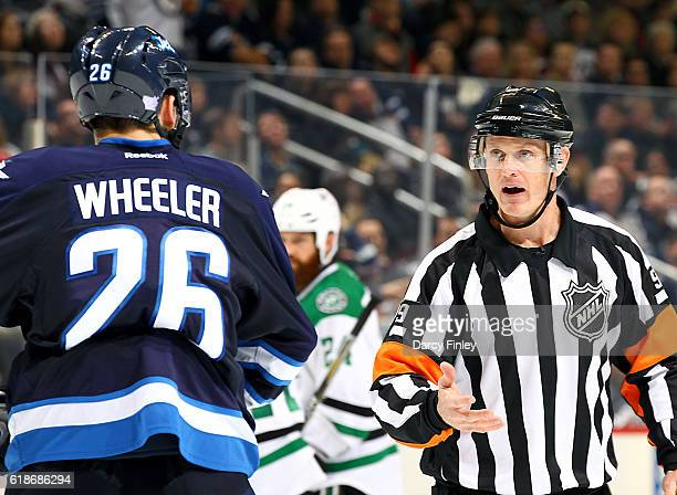 Referee Dan O'Rourke gives an explanation of a call to Blake Wheeler of the Winnipeg Jets during a third period stoppage in play against the Dallas...