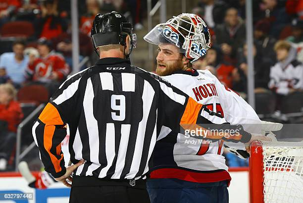 Referee Dan O'Rourke talks to Braden Holtby of the Washington Capitals during the game against the New Jersey Devils at Prudential Center on January...