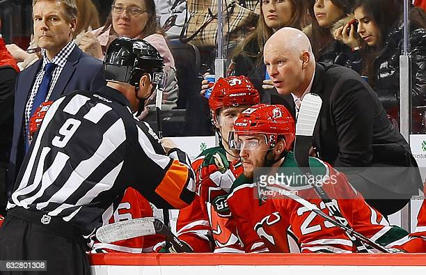 Referee Dan O'Rourke talks with New Jersey Devils head coach John Hynes during the game against the Washington Capitals at Prudential Center on...
