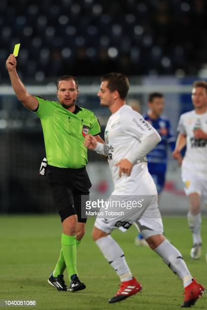 Referee Daniel Muckenhammer issues Kevin Nitzlnader of Wattens a yellow card during the UNIQA OeFB Cup match between TSV Hartberg and WSG Wattens at...