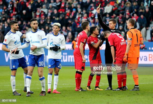 Referee Daniel Siebert 3rd R shows Panagiotis Retsos of Leverkusen t the yellow card and decides for penalty during the Bundesliga match between...