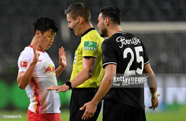 Referee Daniel Siebert gives advise to Leipzig's Hee-chan Hwang and Moenchengladbach's Ramy Bensebaini during the Bundesliga match between Borussia...