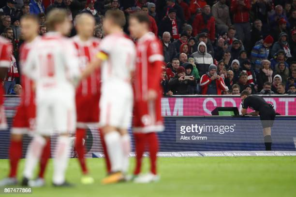 Referee Daniel Siebert looks at the video footage after a foul by Willi Orban of Leipzig which results in a red card during the Bundesliga match...