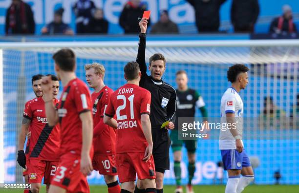 Referee Daniel Siebert shows a red card to Dominik Kohr of Leverkusen during the Bundesliga match between Bayer 04 Leverkusen and FC Schalke 04 at...