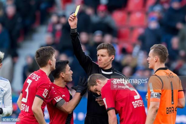 Referee Daniel Siebert shows a yellow card to Panagiotis Retsos of Leverkusen during the Bundesliga match between Bayer 04 Leverkusen and FC Schalke...