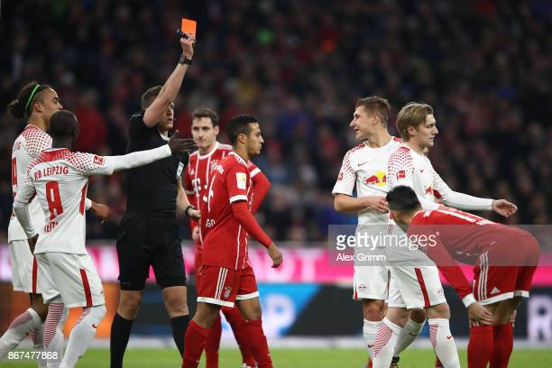 Referee Daniel Siebert shows Willi Orban of Leipzig a red card during the Bundesliga match between FC Bayern Muenchen and RB Leipzig at Allianz Arena...