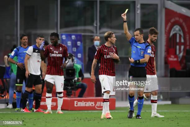 Referee Daniele Doveri issues Lucas Biglia of AC Milan a yellow card for a foul on Ruslan Malinovskyi of Atalanta during the Serie A match between AC...
